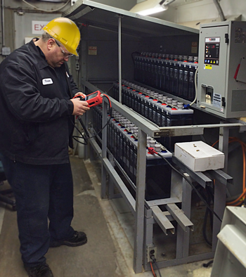 service tech testing stationary batteries with handheld battery analyzer