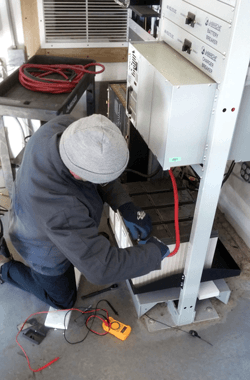 service tech servicing stationary batteries and charger on rack
